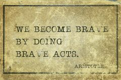Brave acts Aristotle. We become brave by doing brave acts - ancient Greek philosopher Aristotle quote printed on grunge vintage cardboard stock photo