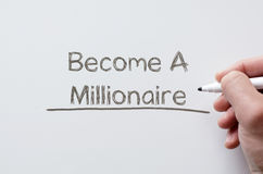 Become a millionaire written on whiteboard. Human hand writing become a millionaire on whiteboard Royalty Free Stock Images