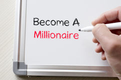 Become a millionaire written on whiteboard. Human hand writing become a millionaire on whiteboard Stock Images