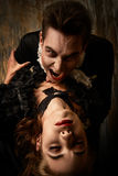 Become undead. Bloodthirsty male vampire in medieval dress is biting a beautiful lady. Halloween Royalty Free Stock Image