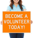Become A Volunteer Today. A woman holding a sign inviting volunteers Royalty Free Stock Image
