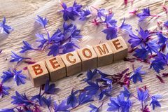 Become on the wooden cubes. Become written on the wooden cubes with blue flowers on white wood stock image