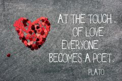Becomes a poet Plato. At the touch of love everyone becomes a poet - ancient Greek philosopher Plato quote printed on blackboard with confetti heart symbol stock images