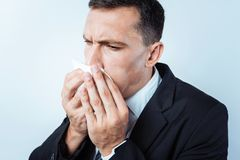 Close up of worried man sneezing. Becoming ill. Scaled up look on a serious office worker using a paper napkin while wanting to sneeze over the light background Stock Images