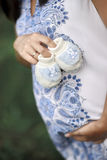 Becoming mum holds little shoes on her belly. Royalty Free Stock Photos
