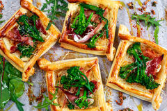 Becon, soft chees and tenderstem broccoli tips puff pastry tarts. Stock Photos