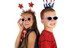 Bedårande pojke och flicka som bär gullig patriotisk solglasögon Arkivfoto