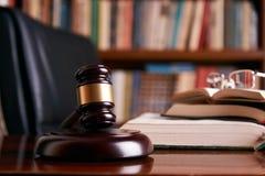Bedöma auktionsklubban eller lagklubban på ett träskrivbord royaltyfri foto