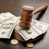 Bedöma auktionsklubban med dollar och eurocent på träskrivbordet Arkivfoto
