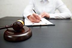 Bedöma auktionsklubban med rättvisaadvokater som har lagmöte på advokatbyrån arkivfoto