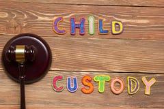 Bedöma auktionsklubban och färgglade bokstäver angående barnarresten, begrepp för familjlag Arkivbilder