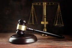 Bedöma auktionsklubban och våg på ett träskrivbord, symbolet för jämvikt och royaltyfria bilder