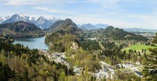 Bedöva alpint landskap med glaciärsjöar, rockerar höga berg och den Hohenschwangau slotten nära berömda Neuschwanstein, Bayern, G royaltyfri fotografi