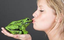 Bedöva blond flicka som kysser en groda Royaltyfri Bild