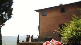 Bedöva brunett kramar hennes man bakifrån som står på balkongen lager videofilmer