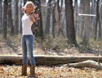 Bedöva den blonda kvinnliga bågskytten - pil som lämnar pilbågen Arkivbilder
