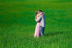 Bedöva den sinnliga utomhus- ståenden av förälskat kyssa för unga stilfulla par för mode attraktiva i sommarfält Royaltyfria Bilder
