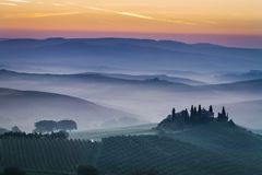 Bedöva dimmiga fält på gryning i Tuscany, Italien royaltyfri foto