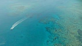 Bedöva flyg- den surrbilden av en liten fiskebåt som in skriver in en ankring för a-havshav i en kanal bredvid en korallrev royaltyfria bilder