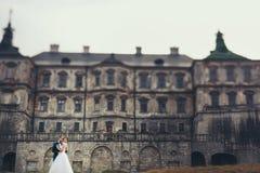 Bedöva gift parkyssar framtill av en gammal slott Arkivfoto