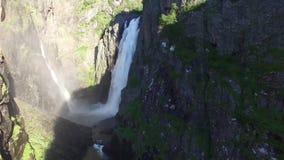 Bedöva 4k som den flyg- surrsikten på den lösa naturstenen vaggar kullen för bergvattenfallklippan som in täckas, sörja träd på s stock video