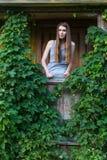 Bedöva kvinnan på en grön terrass i ett landshus Arkivbild