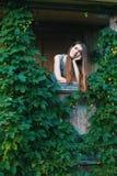 Bedöva kvinnan på en grön terrass i ett landshus Arkivfoton