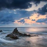 Bedöva landscapedawnsoluppgång med den steniga kustlinjen och lång exp Fotografering för Bildbyråer