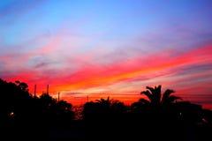 Bedöva röd purpurfärgad solnedgång över en kuststad royaltyfria bilder