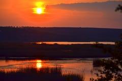 Bedöva rött solnedgångsjölandskap Arkivbilder