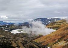 Bedöva rhyoliteberg som slås in i geotermisk ånga som lokaliseras i Landmannalaugaren, Fjallabak naturreserv, centrala Island arkivfoto