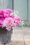 Bedöva rosa pioner i silverhink royaltyfri fotografi