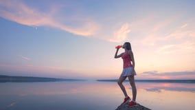 Bedöva sikt av en soluppgångsjö med en ung kvinna som dricker nära den arkivfilmer