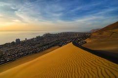 Bedöva sikt till sanddyn, havet och den Iquique staden på solnedgången arkivbild