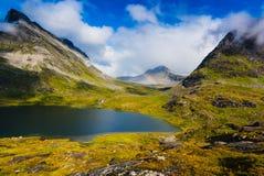 Bedöva sikter av dalen och en sjö med en regnbåge i himlen, väg 63 norway Arkivbild