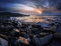 Bedöva solnedgånglandskapbild av den steniga kustlinjen royaltyfri fotografi