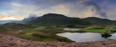 Bedöva soluppgångpanoramalandskap av ljung med berglak Fotografering för Bildbyråer