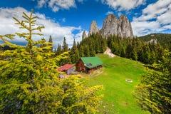 Bedöva sommarlandskap med höga klippor och träkojan, Rumänien fotografering för bildbyråer