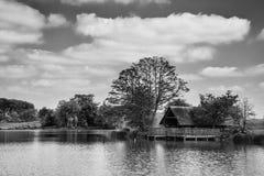 Bedöva svartvit landskapbild av sjöboden på sjön in Arkivfoton