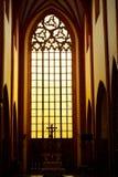 Bedöva ursnyggt solnedgångljus till och med ett gammalt medeltida gotiskt kyrkligt fönster i Europa royaltyfria foton