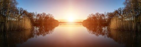 Bedöva vårsoluppgånglandskap över sjön med reflexioner och Arkivbilder