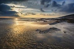 Bedöva vibrerande solnedgånglandskap över Dunraven skälla i Wales Arkivfoto