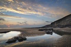 Bedöva vibrerande solnedgånglandskap över Dunraven skälla i Wales Fotografering för Bildbyråer