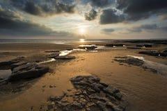 Bedöva vibrerande solnedgånglandskap över Dunraven skälla i Wales Royaltyfri Fotografi