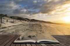 Bedöva vintersoluppgång över den västra Wittering stranden i Sussex England med vind som blåser sand över stranden i sidor av den royaltyfri foto