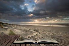 Bedöva vintersoluppgång över den västra Wittering stranden i Sussex England med vind som blåser sand över stranden i sidor av den arkivfoton