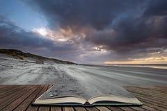 Bedöva vintersoluppgång över den västra Wittering stranden i Sussex England med vind som blåser sand över stranden i sidor av den arkivbilder