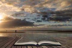 Bedöva vintersoluppgång över den västra Wittering stranden i Sussex England med vind som blåser sand över stranden i sidor av den royaltyfri bild