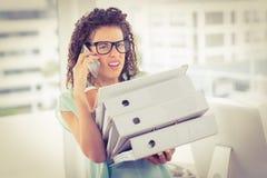 Bedövad affärskvinna som bär en bunt av mappar Royaltyfria Bilder