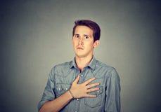 Bedövad man med handen på bröstkorg arkivfoto